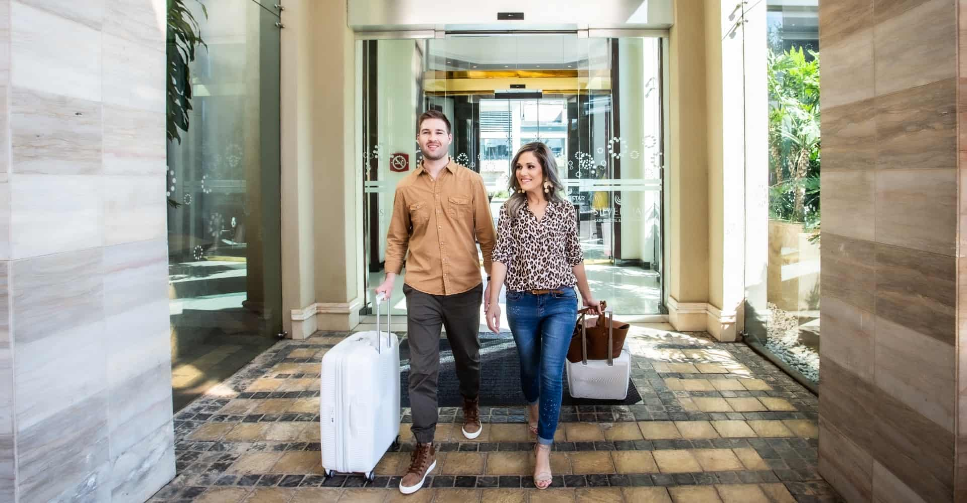Couple walking into Southern Sun Silverstar hotel with luggage