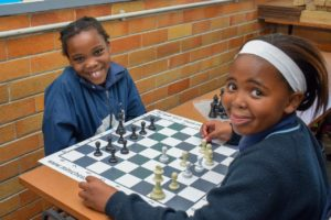 Two girls playing Chess at Hartzstraat Primary