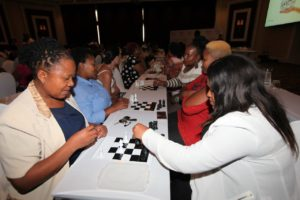 Ladies playing chess at the Silverstar Educator Buzz Chess Tournament